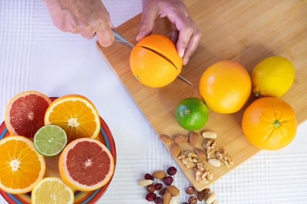 Boven het zicht van de handen van een volwassen vrouw tijdens het snijden van citrusvruchten om gezond sap te maken. gezonde en dieet levensstijl