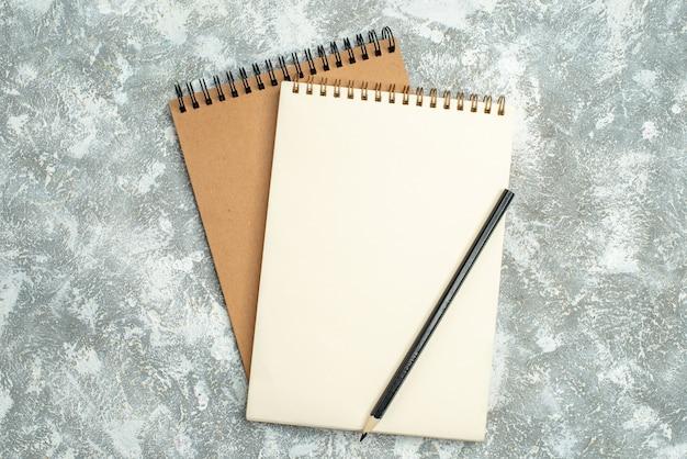 Boven mening van twee kraftpapier-spiraalnotitieboekje met pen op ijsachtergrond