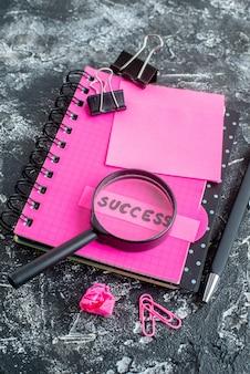Boven menings roze blocnote met pen meer magnifier en succesnota over grijze achtergrond