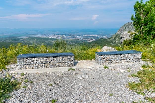 Boven op de berg zijn twee schilderachtige bankjes geplaatst voor een uitzicht over de stad.