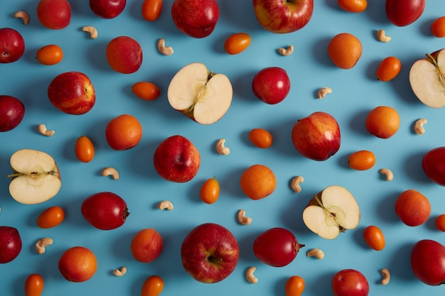 Boven schot van rode rijpe appels, perziken, tomarillo, cumquat en voedzame cashewnoten op blauwe achtergrond. creatieve compositie van heerlijk fruit. zoet voedsel met viamins, gezond voedingsconcept