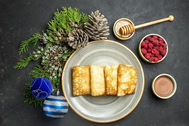 Boven uitzicht op de achtergrond van het diner met heerlijke pannenkoeken, honing en chocolade, framboos en coniferenkegel naast nieuwjaarsaccessoires op zwarte achtergrond