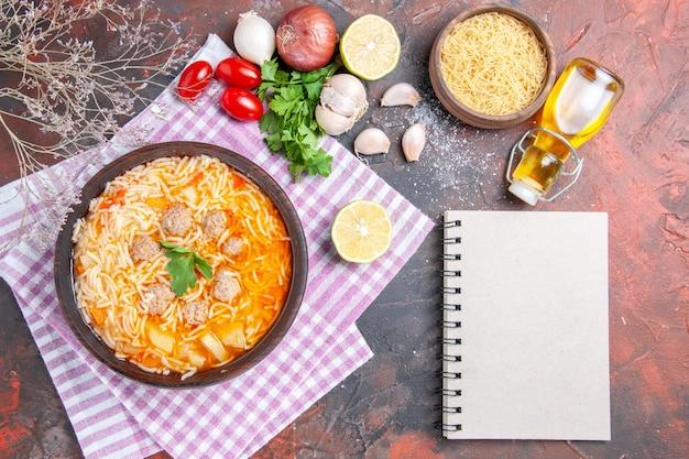 Boven uitzicht op heerlijke kippensoep met noedels greens en lepel op roze gestripte handdoek oliefles knoflook tomaten citroen en notitieboekje op donkere achtergrond