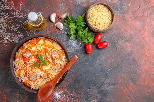 Boven uitzicht op heerlijke noedelsoep met kip en ongekookte pasta in een kleine bruine kom en lepel knoflooktomaten en groene oliefles op de donkere achtergrond