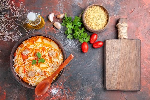 Boven uitzicht op heerlijke noedelsoep met kip en ongekookte pasta in een kleine bruine kom en lepel knoflooktomaten en groene snijplank op de donkere achtergrond