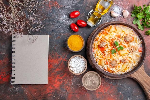 Boven uitzicht op heerlijke noedelsoep met kip op houten snijplank, oliefles, verschillende kruidengroenten en notitieboekje op donkere tafel
