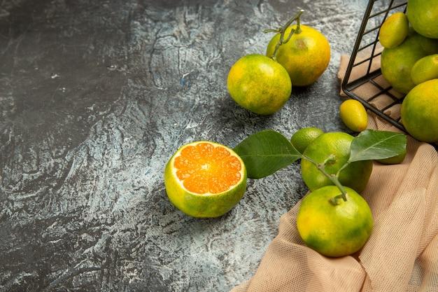Boven uitzicht op verse kumquats en citroenen in een gevallen zwarte mand op handdoek en vier citroenen op grijze tafel