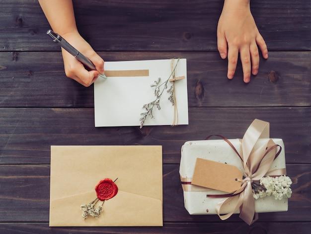 Boven van hand meisje schrijven kaart en ambachtelijke geschenkdoos op houten tafel achtergrond