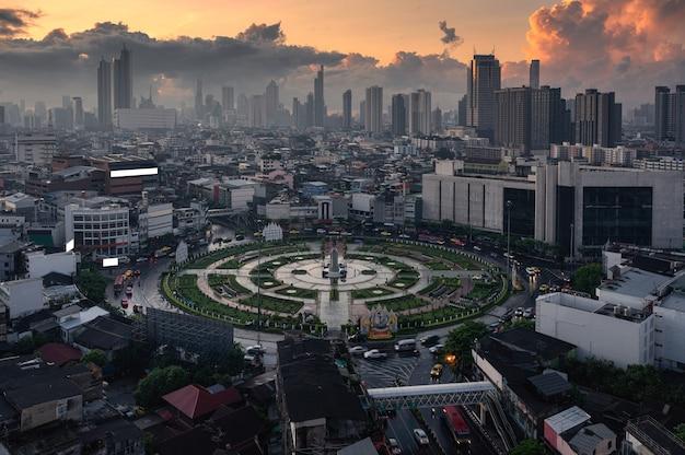Boven van wongwianyai rotonde monument met autoverkeer en wolkenkrabber in het centrum van bangkok