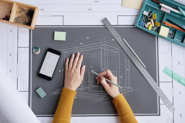 Boven weergave achtergrond van vrouwelijke architect tekening blauwdrukken en plannen zittend aan een bureau in kantoor,