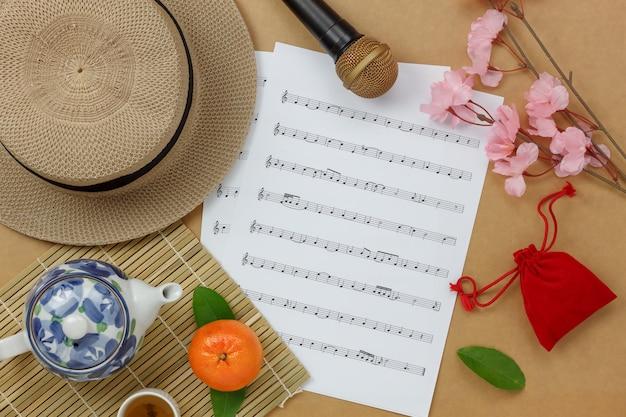 Boven weergave chinees & maannieuwjaar met muziekblad notities concept achtergrond. kopie ruimte voor creatief ontwerp tekst of lettertype. difference objecten op het moderne rustiek bruin houten bureau aan huis.