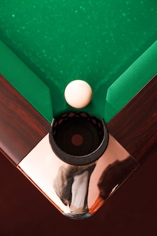 Boven weergave op biljartbal tegenover een pocket.