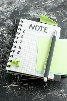 Boven weergave open blocnote met pen en notitie schrijven op grijze achtergrond