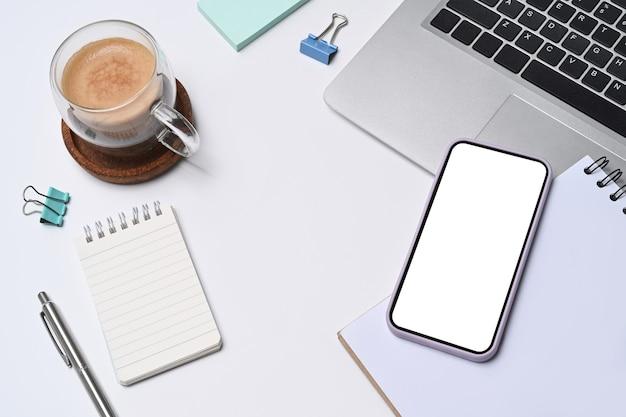 Boven weergave slimme telefoon, kopje koffie, laptopcomputer en notitieblok op wit bureau.