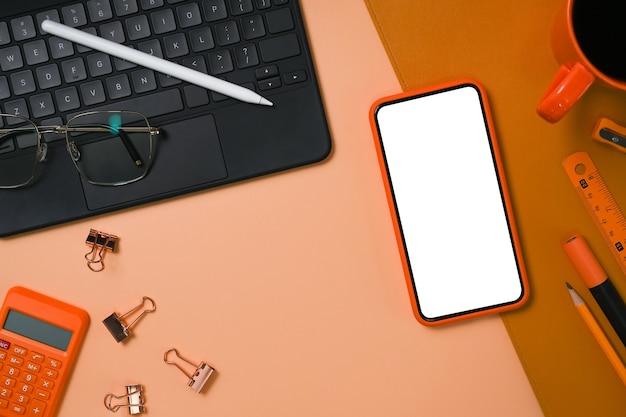 Boven weergave slimme telefoon, rekenmachine, computer laptop en briefpapier op beige achtergrond.