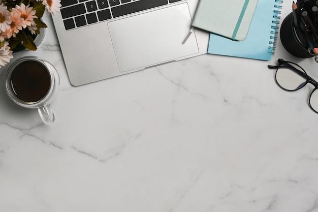 Boven weergave stijlvolle werkruimte met laptopcomputer, notebook en koffiekopje op marmeren achtergrond.