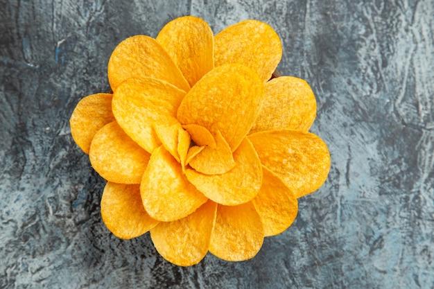 Boven weergave van aardappelchips versierd als bloem gevormd in een bruine kom op grijze tafel