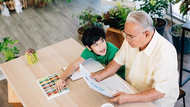 Boven weergave van aziatische pensioneringsgrootvader en zijn kleinzoon die quality time samen thuis geïsoleerd doorbrengen.