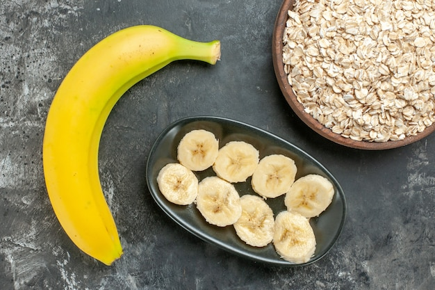 Boven weergave van biologische voedingsbron verse banaan gehakt en geheel en haverzemelen in een bruine pot op donkere achtergrond