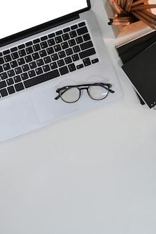 Boven weergave van bureau met laptopcomputer, bril, notebook en kopieerruimte.