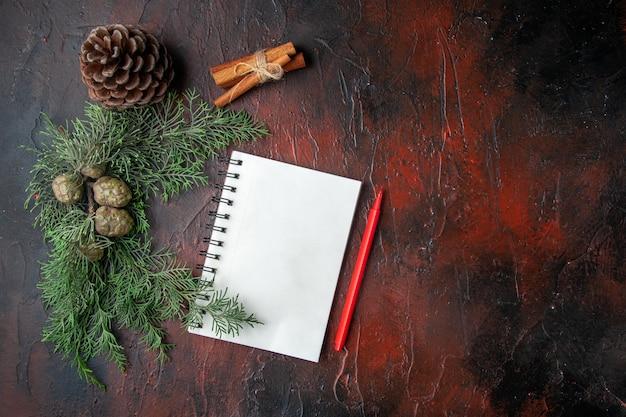 Boven weergave van dennentakken en gesloten spiraalvormig notitieboekje met pen kaneel limoenen conifer kegel op donkere achtergrond