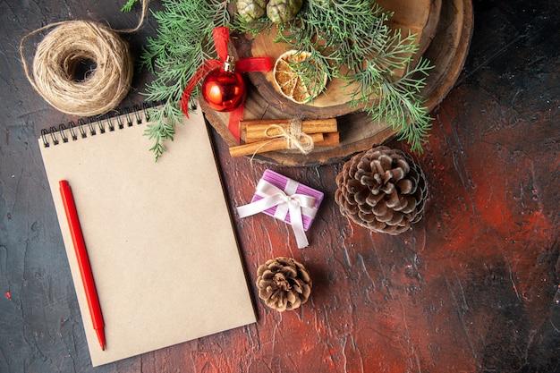 Boven weergave van dennentakken en gesloten spiraalvormig notitieboekje met pen, kaneellimoenen, coniferenkegel en bal van touw op donkere achtergrond