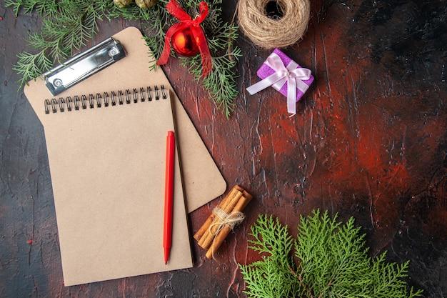 Boven weergave van dennentakken, kaneellimoenen cadeau en notitieboekje op donkere achtergrond