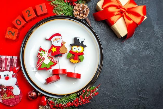 Boven weergave van diner plaat decoratie accessoires fir takken en nummers kerst sok op een rood servet naast cadeau op een zwarte tafel