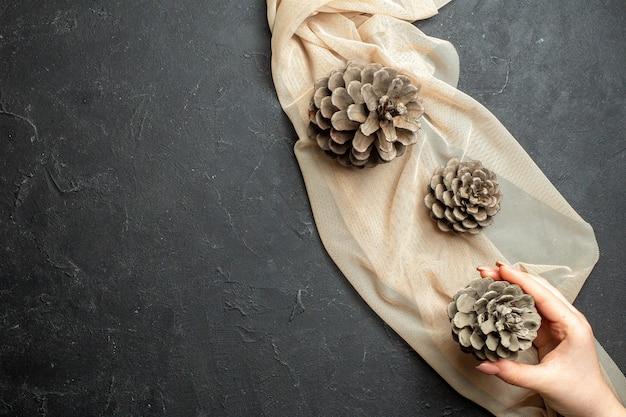Boven weergave van drie coniferen kegels op naakt kleur handdoek op zwarte kleur achtergrond