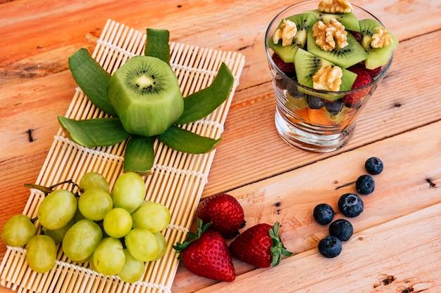 Boven weergave van een gemengde en frisse kleurrijke fruitsalade in een glazen beker. vers fruit op de achtergrond op een houten tafel