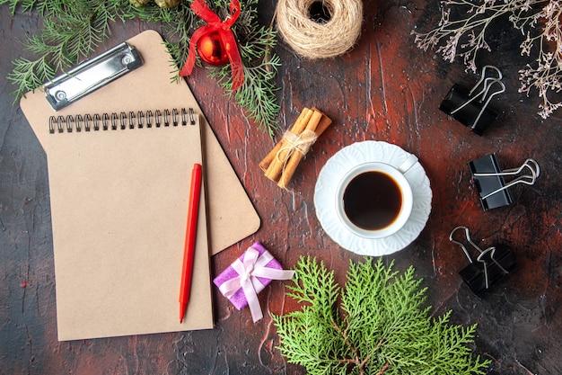 Boven weergave van een kopje zwarte thee dennentakken kaneel limoenen conifer kegels geschenk en notitieboekje op donkere achtergrond