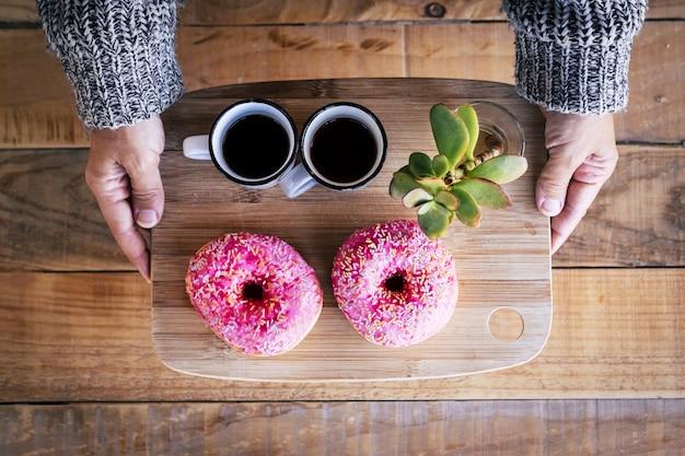 Boven weergave van een paar blanke vrouwelijke handen die een houten bord nemen met twee gebrek aan italiaanse koffie en een paar roze suikerdonuts.