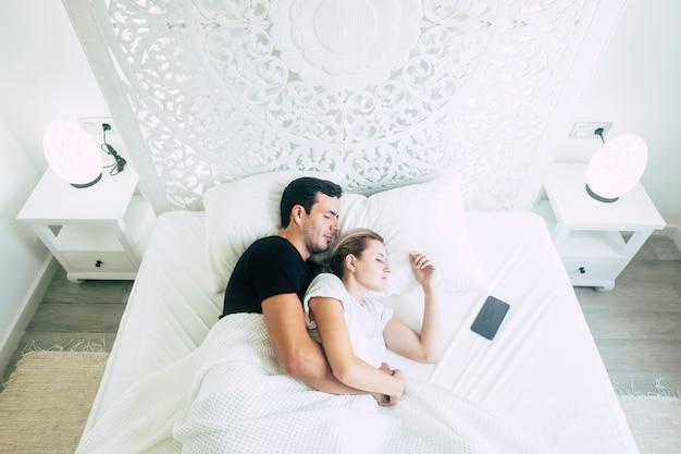 Boven weergave van een paar mooie jonge mensen, mannen en vrouwen slapen samen in de slaapkamer op het bed