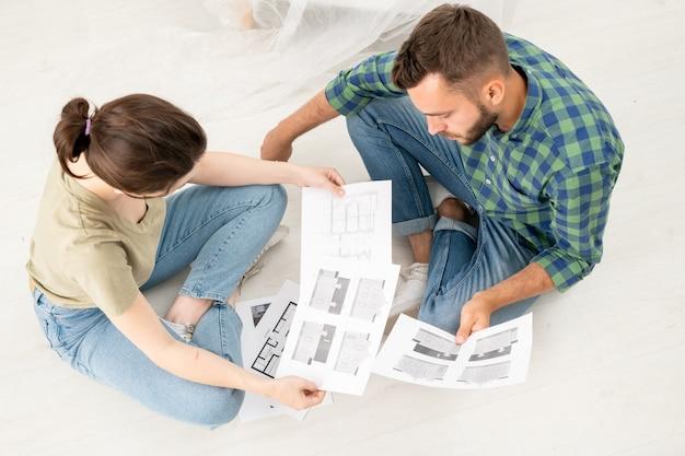 Boven weergave van geconcentreerde jonge paar zittend met gekruiste benen op de vloer en het analyseren van huisplannen tijdens het denken over renovatie