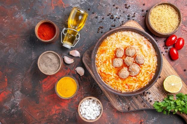 Boven weergave van gehaktballensoep met noedels, ongekookte pasta, snijplank, citroen, een bos groene tomaten, verschillende kruiden op donkere tafel