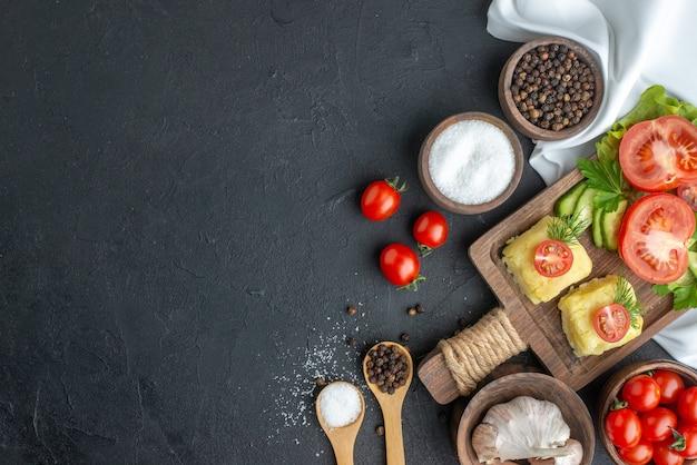 Boven weergave van gehakte en hele verse groenten op snijplank in kommen en kruiden op witte handdoek op zwarte ondergrond