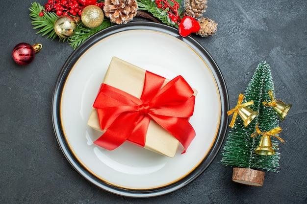 Boven weergave van geschenkdoos op diner plaat kerstboom fir takken naaldboom kegel op zwarte achtergrond