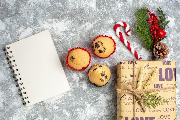 Boven weergave van gesloten notitieboekje en kleine cupcakes mooi verpakt kerstcadeau met liefdesinscriptie en dennentakken decoratie accessoires conifer kegel aan de linkerkant op ijsoppervlak
