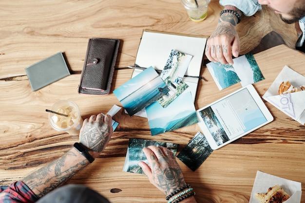 Boven weergave van getatoeëerde mannen die aan een houten tafel zitten en samen schilderachtige foto's bekijken, herinneringen over het reisconcept