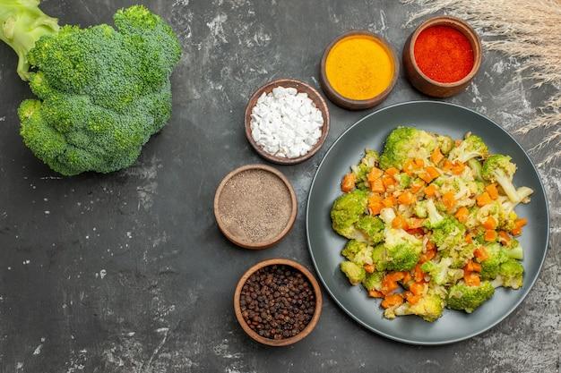 Boven weergave van gezonde maaltijd met brocoli en wortelen op een zwarte plaat en kruiden op grijze tafel