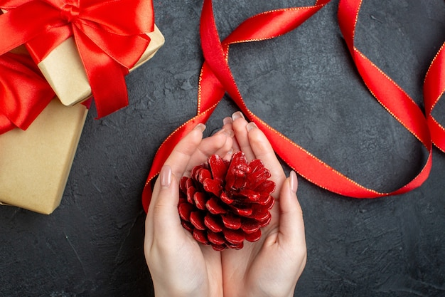 Boven weergave van hand met een coniferen kegel en mooi cadeau op donkere achtergrond