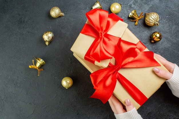 Boven weergave van hand met een van geschenkdozen met rood lint en decoratie accessoires op donkere achtergrond