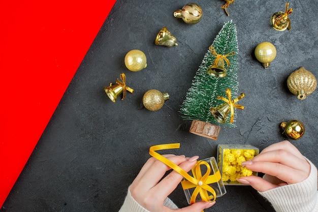 Boven weergave van hand met geschenkdozen en kerstboom decoratie accessoires op donkere achtergrond