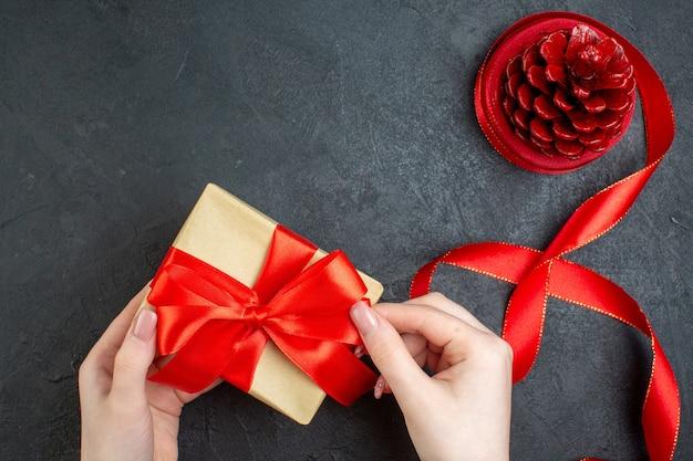 Boven weergave van hand met mooi cadeau en conifer kegel op donkere achtergrond