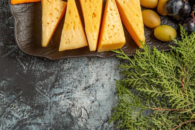 Boven weergave van heerlijke beste snack voor wijn op bruin dienblad en dennentakken op ijsachtergrond
