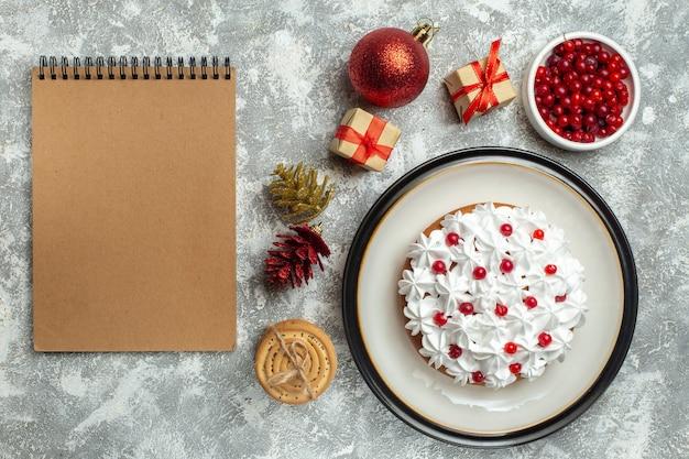 Boven weergave van heerlijke cake met roombes op een bord en geschenkdozen