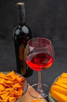 Boven weergave van heerlijke chips binnen en buiten de kom en rode wijn in een glas op een oude krant