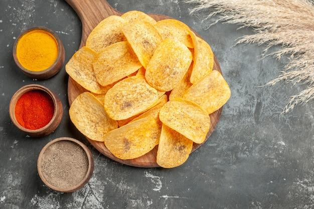 Boven weergave van heerlijke chips kruiden met ketchup op grijze tafel