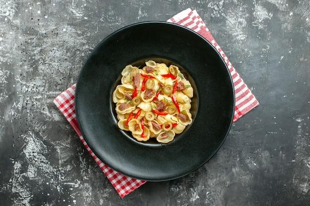 Boven weergave van heerlijke conchiglie met groenten op een bord en mes op rode gestripte handdoek op grijze achtergrond