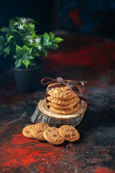 Boven weergave van heerlijke gestapelde koekjes vastgebonden met lint op houten plank en bloempot op donkere mix kleuren achtergrond
